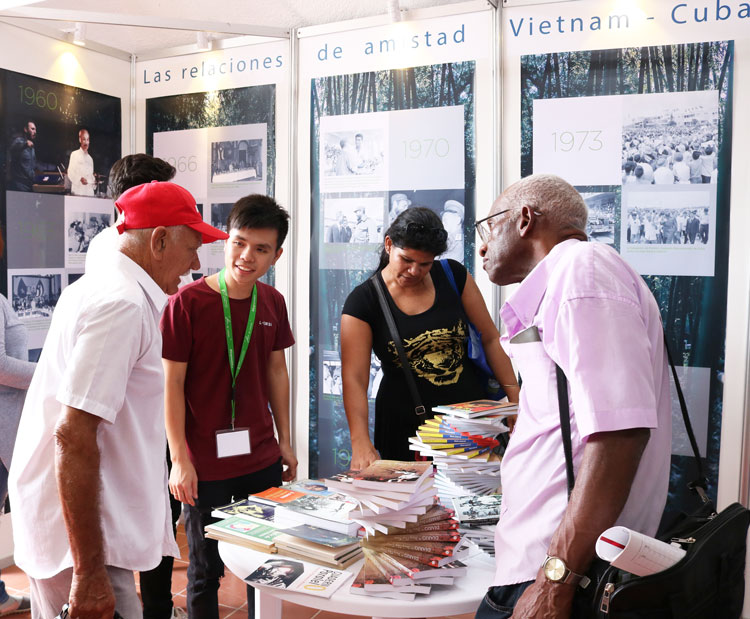 Cubans browse books at Vietnamese pavilion at Havana Book Fair. Displays depict Cuba's solidarity with Vietnam and its battle for independence and unification against Washington's war.
