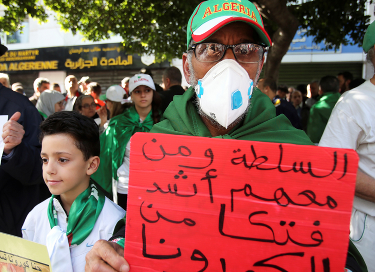 """Demonstrators at Feb. 28 anti-government protest in Algiers. Placard reads: """"The authority and its supporters are deadlier than the coronavirus."""" After year of massive protests, military-dominated regime used justification of virus crisis to ban demonstrations March 17."""