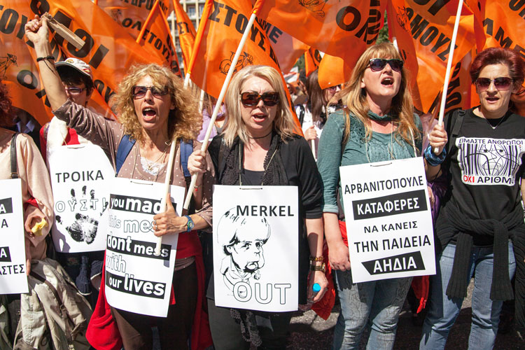 """Greek teachers protest against layoffs in Athens, March 21, 2014. """"Merkel out"""" sign shows anger over Berlin's demand that Athens impose greater """"austerity"""" on working people to get new EU loans. In 2018, Greek rulers agreed to restrictions on social spending for next 40 years!"""