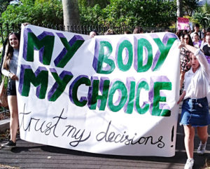 Holly Wakelin, left, and Lucy Mackenzie, right, two young women who helped lead recent actions for women's right to abortion, hold banner at Auckland Feb. 18 march. After decades of mobilizations, New Zealand's parliament adopted law legalizing abortion March 18.