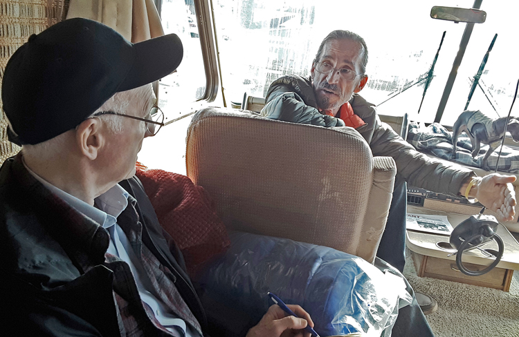 Joel Britton, left, currently SWP candidate for U.S. Congress, speaks with carpenter Tony Worino in his RV at Camp Fire refugee camp in Chico, California, in December 2018.
