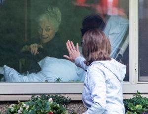 "Lori Spencer waves to her 81-year-old mother through window at Seattle aged care facility March 11. Capitalist rulers' ""social distancing"" restrictions increase isolation by shutting down sorely needed meetings of Alcoholics Anonymous and visits to elderly in care homes."