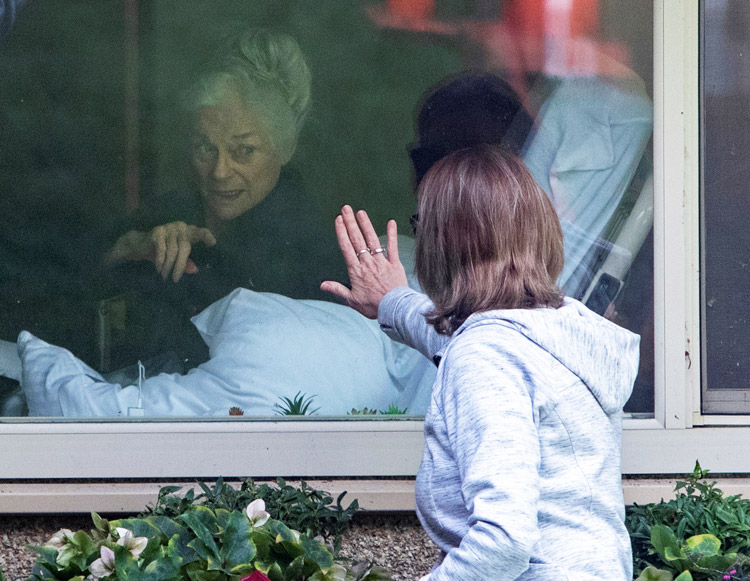 """Lori Spencer waves to her 81-year-old mother through window at Seattle aged care facility March 11. Capitalist rulers' """"social distancing"""" restrictions increase isolation by shutting down sorely needed meetings of Alcoholics Anonymous and visits to elderly in care homes."""