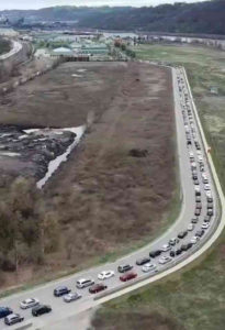 """Miles of cars wait to get to Pittsburgh community food bank March 30. Tini Mason, 44, just out of job as a cook, said it was a """"mind-blowing experience I will never forget."""""""
