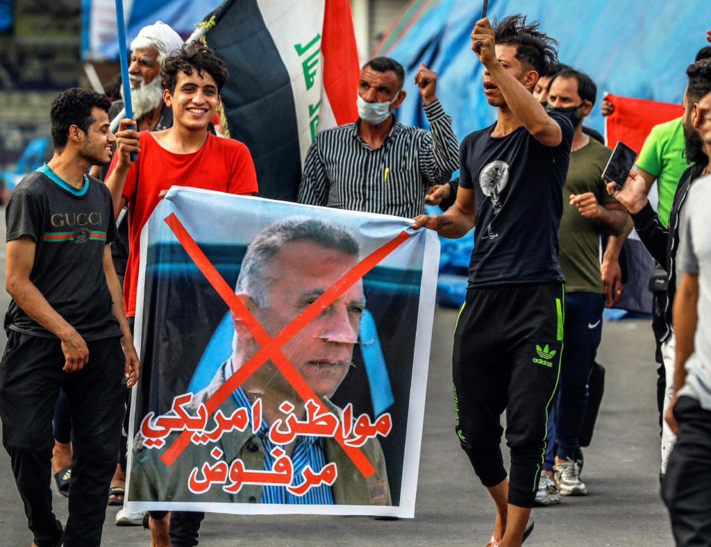 Anti-government demonstrators in Baghdad April 9 march against appointment of Mustafa al-Kadhemi, Iraq government's spy master, as prime minister, with his picture crossed out.