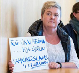 """Solveig Anna Jonsdottir, chair of Efling Union and a cleaner, holds sign at May 5 union meeting: """"I work at home ... other people's homes, without a contract for 13 months."""""""