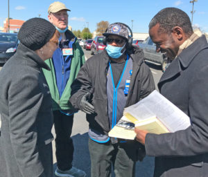 Socialist Workers Party presidential candidate Alyson Kennedy, left, and vice presidential candidate Malcolm Jarrett, right, speak with Walmart worker Otis Bullock in Philadelphia.