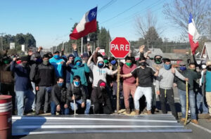 "Road blocked by some of 500 workers in 43-day strike at Promasa, a lumber company in Los Ángeles, Chile, one of number of recent strikes and protests. Mass anti-government protests that began in October ""are going to explode again soon,"" union leader at Holdtech strike predicted."