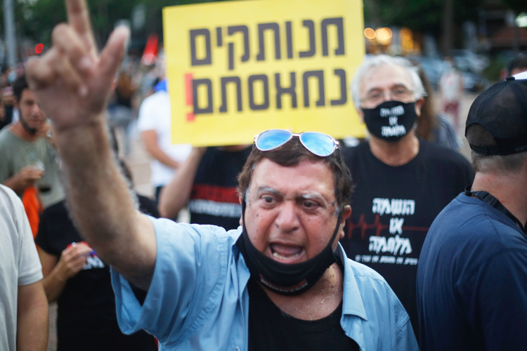 "Tens of thousands protest July 11 in Tel Aviv, Israel, against government's failure to deliver aid promised to workers classified as self-employed. Sign reads, ""Out of touch! We're fed up!"""