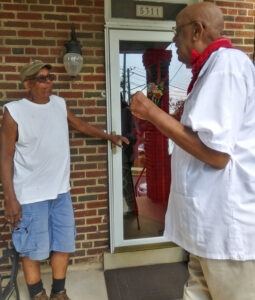 Omari Musa, right, SWP candidate for D.C. Congress delegate, speaks with retired worker James Cunningham June 27.