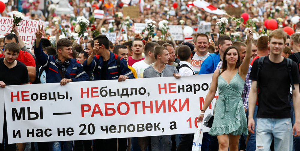 "Thousands of working people march from Minsk tractor factory to Belarus parliament Aug. 14. Banner answers President Lukashenko's attacks, saying: ""We're not sheep. ... We are MTZ workers, we are not 20 people, we are 16,000!"" Inset, like many disgusted at violent attacks on demonstrators, soldier had himself filmed throwing his uniform away into the garbage."