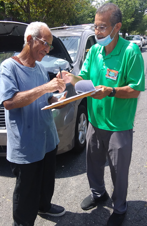 Campaign supporter Nelson Gonzalez, at right, signs people up in Bayonne, New Jersey.