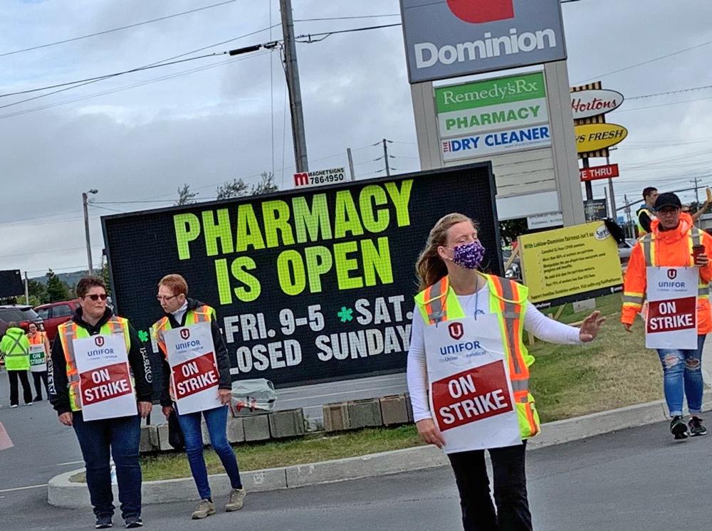 Ligne de piquetage des travailleurs de Dominion, en grève depuis le 22 août, à Bay Roberts, à Terre-Neuve, le 13 septembre. La décision de la compagnie de mettre fin à la prime de risque de 2 $ l'heure « a été une claque dans la face, » a dit une gréviste.