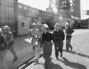 Women coal miners from U.S. visit British coalfields in 1987, to learn about miners' resistance. As millions of jobs are erased today and wages and working conditions come under attack, the bosses of the cosmetics industry come in to try and boost profits off women's insecurities.
