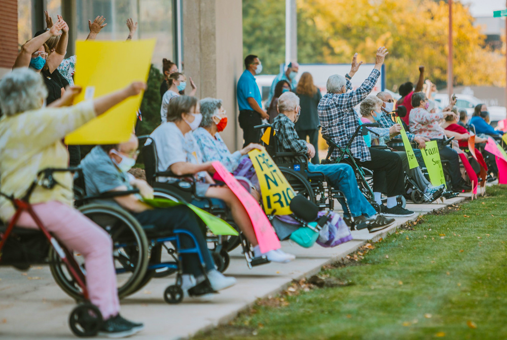 Fairacres Manor nursing home residents in Greeley, Colorado, backed by nursing staff, protest restrictions imposed on physical contact with loved ones Oct. 8. Rulers have shunted elderly into overcrowded, understaffed nursing homes, leaving thousands shut in to die.