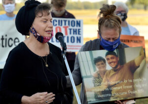 Lisa Brown, mother of Christopher Vialva, speaks at anti-death-penalty rally Sept. 24 at federal prison in Terre Haute, Indiana, hours before her son was executed. Poster shows his picture.
