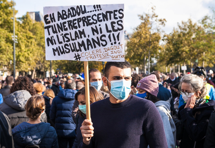 """Sign at Paris rally Oct. 18 says, """"Hey Abadou, you do not represent Islam or Muslims,"""" referring to killer of Samuel Paty. Government is attempting to use anger at killing to weaken political rights."""