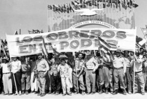 "In 1960, workers' initiatives nationalizing U.S. and other capitalist firms were backed by Cuban revolutionary government. Havana May Day banner in 1961 declared ""Workers in power."""