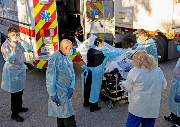 Hospital workers move bodies into refrigerated trailer in El Paso, Texas, Nov. 16. Shortage of beds, staff, equipment in for-profit hospital system increases toll of coronavirus pandemic.