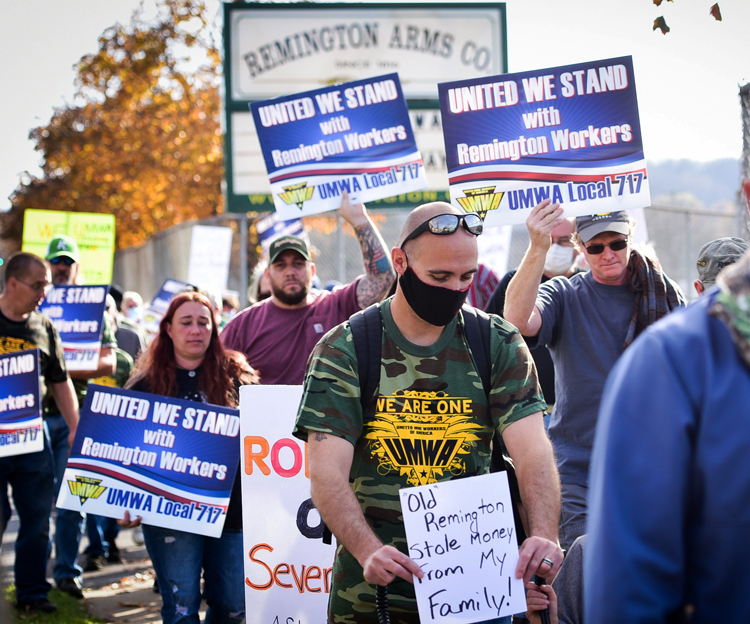 Workers march in Ilion, New York, Nov. 7, demand Remington Arms Co. honor union contract, give severance and vacation pay after plant shut down. Millions in U.S. have lost jobs.