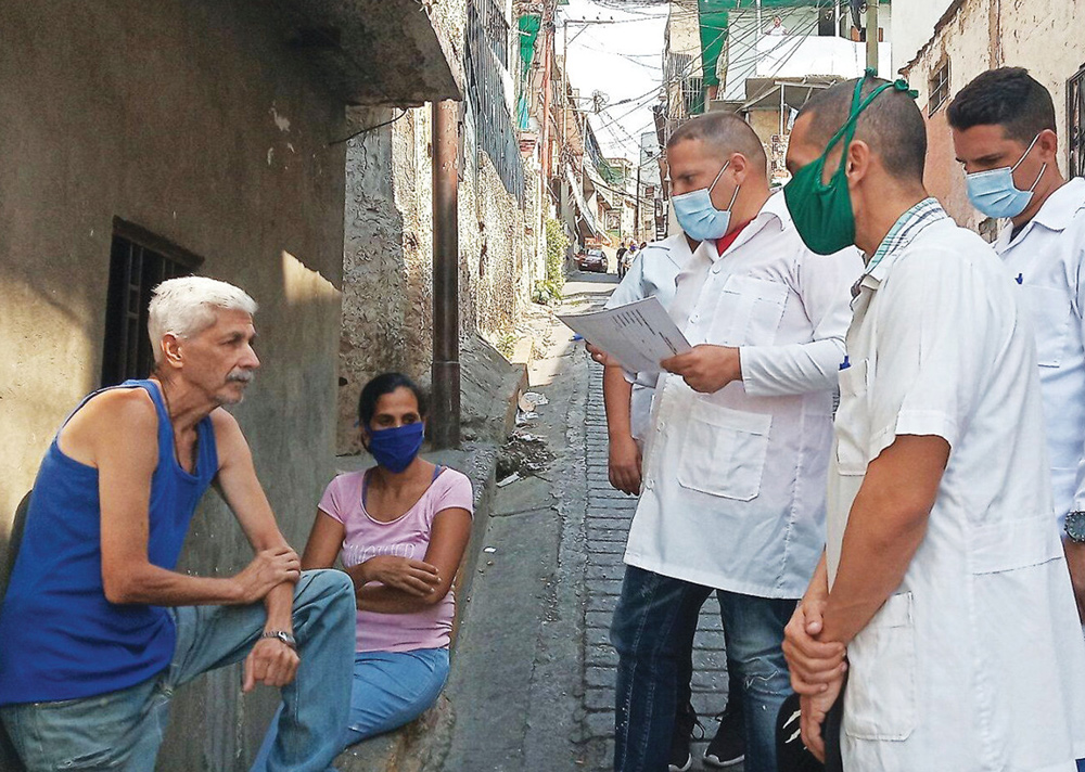Volunteer Cuban doctors treat working people for symptoms of COVID-19 in Caracas in April. Revolutionary Cuba defends Venezuelan sovereignty against U.S. sanctions, attacks.