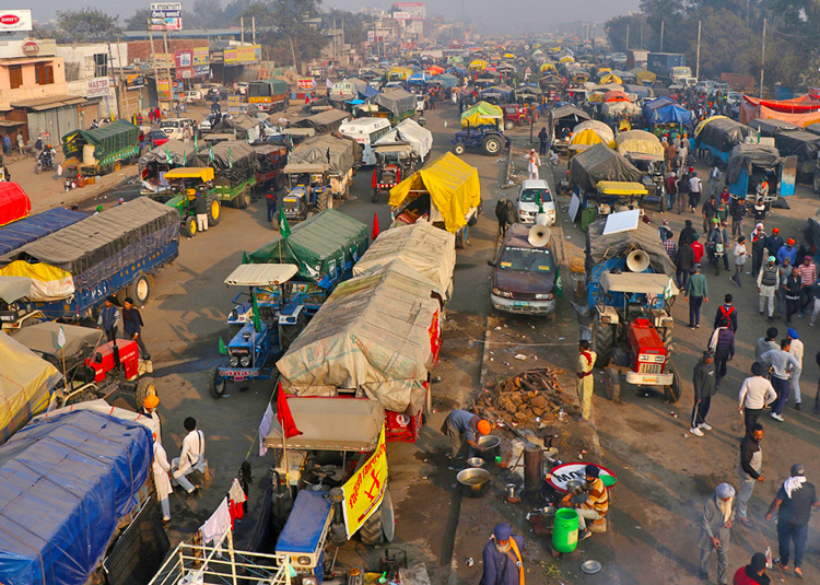 Tens of thousands of farmers in camp near Indian capital New Delhi protest government assault on their livelihoods. Inset, car caravan in Montreal Dec. 12 in solidarity with farmers' actions.