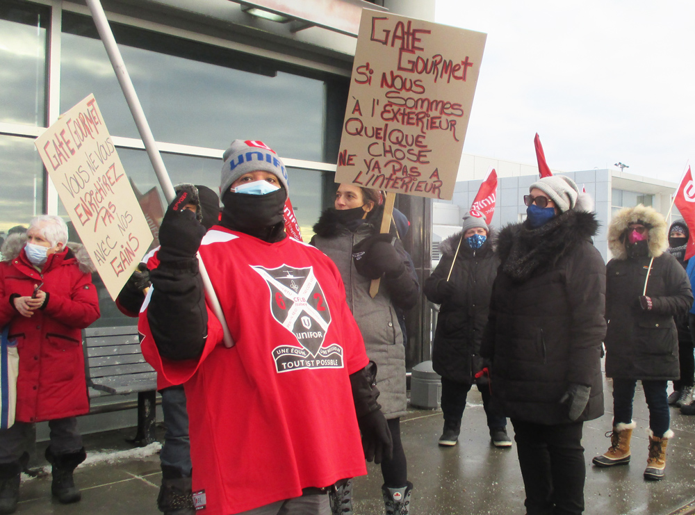 "Airline catering workers organized by Unifor Local 698 protest eight-week lockout by Gate Gourmet at airport in Montreal Dec. 31. Placard on right says, ""If we are on the outside, something is wrong on the inside."" One on left says, ""You don't get rich on our earnings."""
