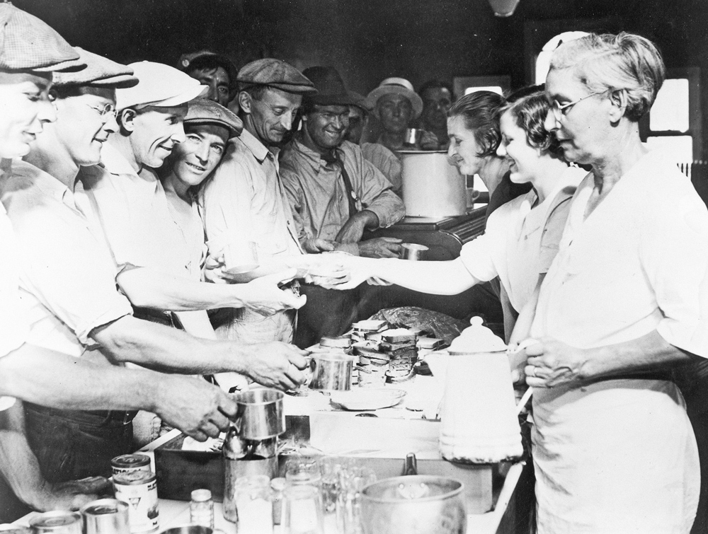Teamsters Local 574 Women's Auxiliary volunteers serve meals during 1934 Minneapolis strike. They also treated wounded picketers in strike hospital, spoke widely in region to win support.