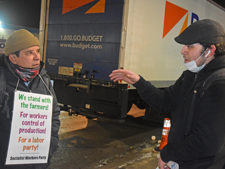 "Róger Calero, left, SWP candidate for mayor of New York, with Alberto Mendoza, a worker at Hunts Point Produce Market, Feb. 10. ""The bosses use the unemployed to drive down our wages,"" Mendoza told Calero. ""Then they tell us, if you don't like it, there's the front door!"""