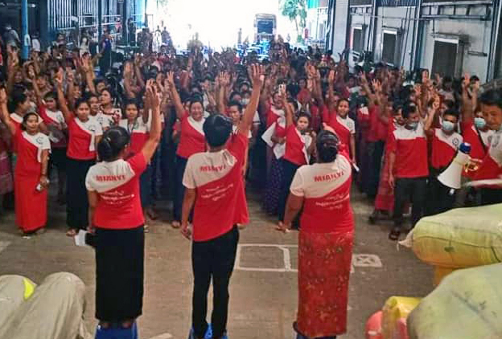 Garment workers inside factory in Myanmar raise three finger salute, a symbol of defiance against military coup, Feb. 5. Mass protests and strikes exploded in face of military crackdown.