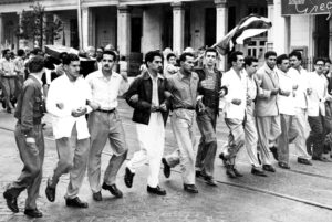 University students march in Havana against Fulgencio Batista's U.S.-backed dictatorship, April 6, 1952, a month after he overthrew the elected government in a coup. Armando Hart is sixth from left, looking at the camera. Behind, waving Cuban flag, is Raúl Castro.