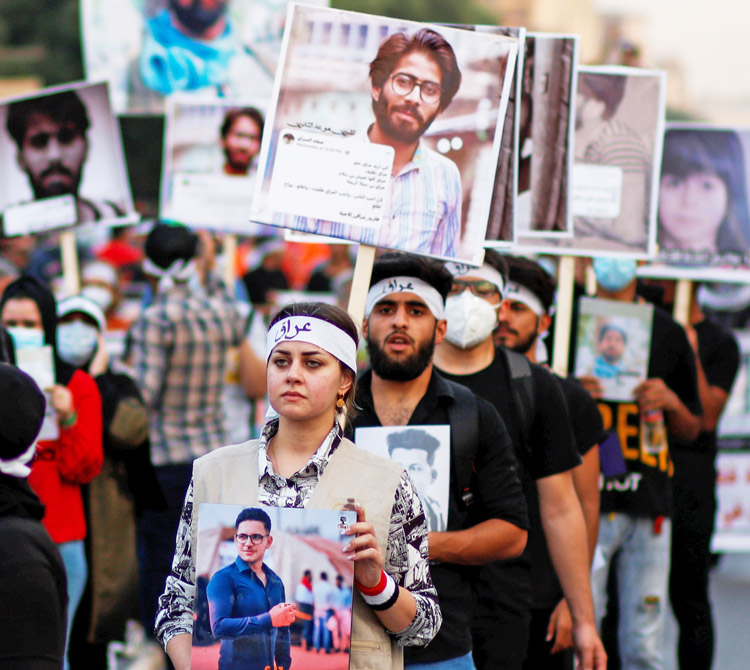 Protesters in Baghdad, Iraq, Oct. 28, 2020, carry photos of some of 600 people killed by security forces during anti-government actions.
