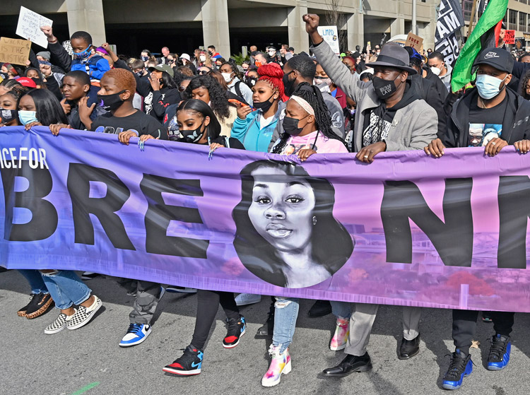 Tamika Palmer, center, marches behind banner with portrait of her daughter Breonna Taylor, in Louisville March 13 on first anniversary of fatal shooting by police. Hundreds who took part demanded the cops responsible face criminal charges over her killing.