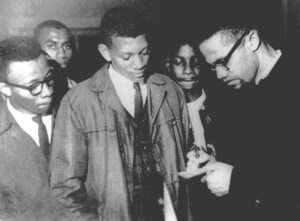 "Malcolm X talks to students at Tuskegee Institute in Alabama, Feb. 3, 1965. Two months earlier at Oxford University in the U.K. he said, ""I will join with anyone, I don't care what color you are, as long as you want to change this miserable condition that exists on this earth."""