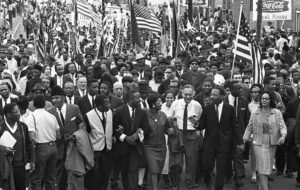Demonstrators cross Edmund Pettus Bridge out of Selma, March 21, 1965, after victory in fight to march to state capital in Montgomery. Inset, days earlier, sheriff's deputies attack protesters in Montgomery. Second from right is John Studer, who came to join the historic protests from Ohio. Stu-der is now editor of the Militant.