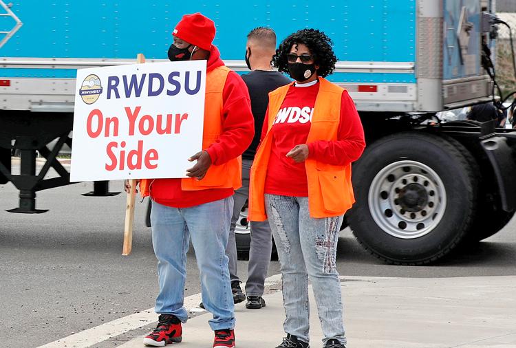 Le 5 mars, des travailleurs portent des pancartes devant le centre de distribution d'Amazon, à Bessemer en Alabama, pour appuyer la campagne de syndicalisation du Syndicat de commerces de détail, d'entrepôts et de grandes chaînes.