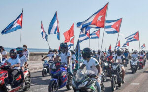 """As part of international day of protest against Washington's embargo against Cuba, motorcyclists ride along Havana's famous Malecón esplanade March 28. They, and others in cars and on bicycles, chanted, """"Down with the blockade!"""" as they passed the U.S. Embassy."""