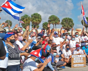 """Some of the participants from March 28 caravan protest in Miami rally at the end of a drive through Coral Gables and the """"Little Havana"""" area of the city. Placard at right says, """"Homeland and life! Down with the blockade! Long live Cuba."""" Action was fourth straight monthly protest"""