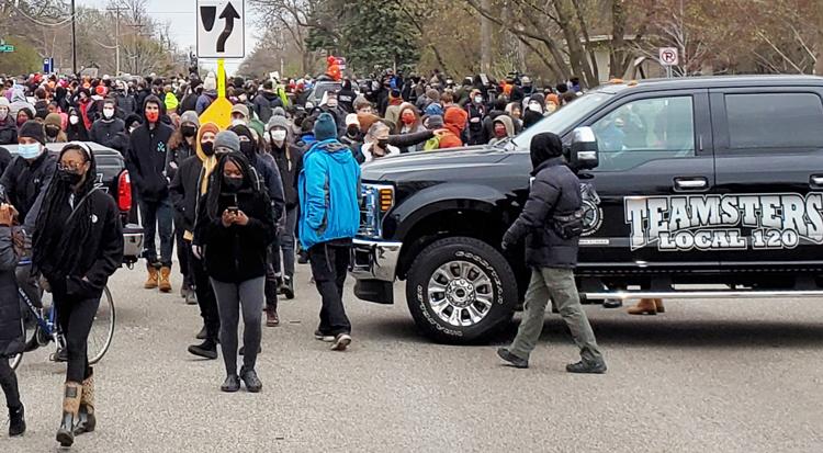 """Miles se unen a vigilia el 12 de abril para Daunte Wright, muerto a manos de policías de Brooklyn Center, Minnesota. El Local 120 del sindicato Teamsters, la unión de trabajadores despedidos en huelga contra Marathon Petroleum, usaron camionetas del sindicato para ayudar a cerrar la calle (arriba). Abajo, Doug Nelson, candidato del Partido Socialista de los Trabajadores para alcalde de Minneapolis con cartel que dice: """"Juzgen al policía asesino""""."""