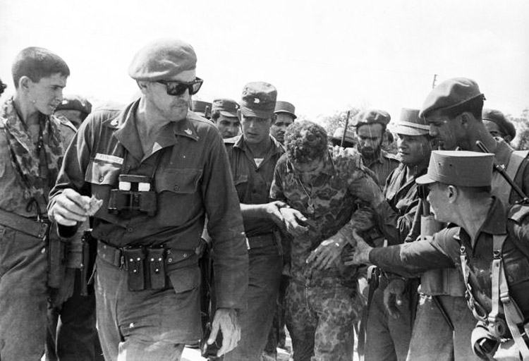 "José Ramón Fernández walks ahead of Cuban soldiers aiding captured mercenary in April 1961. U.S.-backed invasion was ""well organized, well armed and well supported, but lacked a just cause to defend,"" Fernández said. ""Firm support for the revolution and Fidel was decisive."""