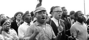 """Martin Luther King (arriba, centro), y John Lewis (der.) en marcha de Selma a Montgomery tras cruzar puente Edmund Pettus el 21 de marzo de 1965. Recuadro, """"Domingo Sangriento"""", cuando Lewis fue golpeado en el puente. Pettus fue un general de la Confederación y líder del KKK. En 2015, Lewis se opuso a que se cambiara el nombre del puente. Dijo, """"simboliza lo que fuimos una vez, y en lo que nos hemos convertido hoy""""."""