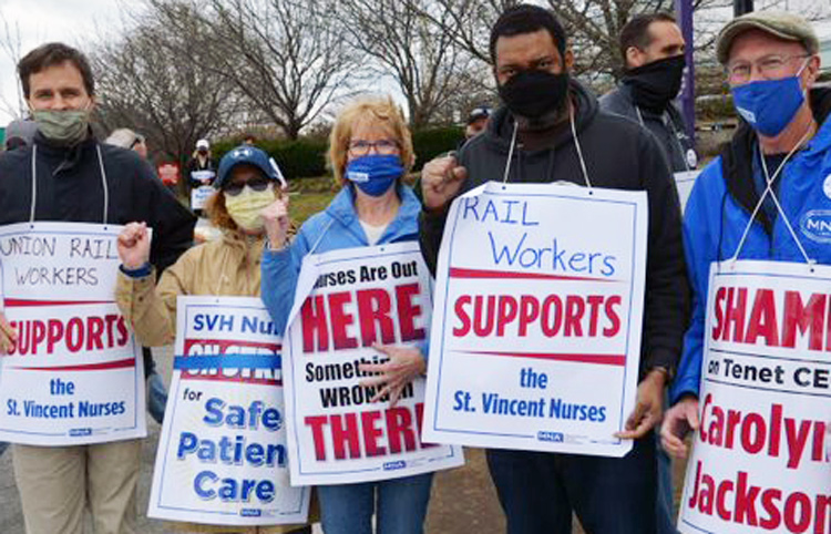 """Nurses' strike """"is about safe care,"""" nurse Bill Lahey, right, told rail workers Jacob Perasso, left, and Joe Allen, second from right, in Worcester, Mass., March 31."""