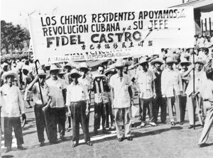 """Resident Chinese support the Cuban Revolution and its leader, Fidel Castro!"" is banner of Chinese New Democracy Alliance as they join a million people in Havana, Sept. 2, 1960. Rally approved Declaration of Havana, affirming duty of oppressed peoples to fight for liberation."