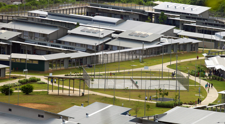 """Above, immigration detention center on Christmas Island, remote Australian territory in Indian Ocean. Hundreds of """"501 detainees"""" are imprisoned there, facing deportation under Canberra's law using """"character grounds"""" to cancel visas of long-term residents. The law especially targets workers from New Zealand. Left, a fire at compound Jan. 10 after several days of sit-in protesting indefinite detention without family visits or contact with anyone."""