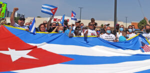 Above, participants in Miami caravan rally around Cuban flag April 25 after caravan through Little Havana.