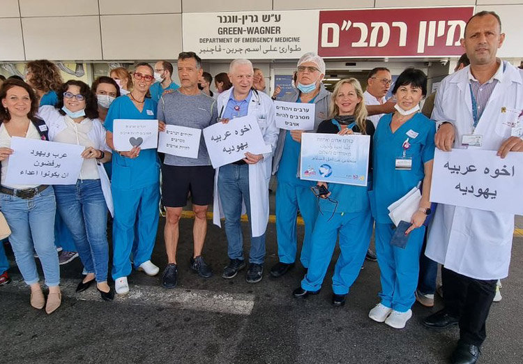 """Jewish and Arab workers at Rambam Health Care in Haifa, hold Arabic and Hebrew signs May 16 saying """"Jews and Arabs refuse to be enemies."""" This is key to class-struggle road forward."""