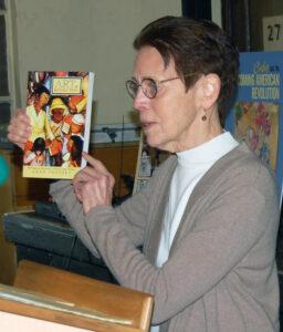 Mary-Alice Waters, dirigente del PST, muestra mural de Diego Rivera con maestra solitaria durante revolución burguesa mexicana, que aparece en portada de Arte y revolución de León Trotsky. Lo contrastó con la campaña de alfabetización de la Revolución Cubana, que movilizó a 100 mil jóvenes y transformó su conciencia de clase.