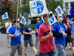 Over 150 people in Longueuil, near Montreal, march outside ArcelorMittal headquarters May 21 to support iron ore miners on strike in Port-Cartier and Fermont in northern Quebec.