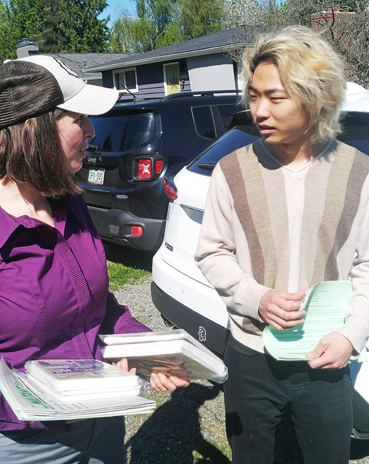 """Rebecca Williamson, SWP Seattle City Council candidate, speaks with James Lee, in North Seattle April 20. """"Capital-ism makes its own gravediggers,"""" Williamson told him."""