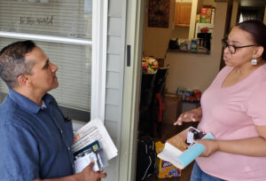 Ved Dookhun, SWP candidate for mayor of Albany, speaks to Francesca Jones on her porch May 21. Jones subscribed to Militant, got Malcolm X, Black Liberation, and the Road to Workers Power.